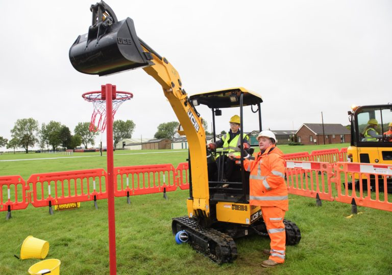 Young child operating a yellow JCB digger with man in orange high clothing supervising