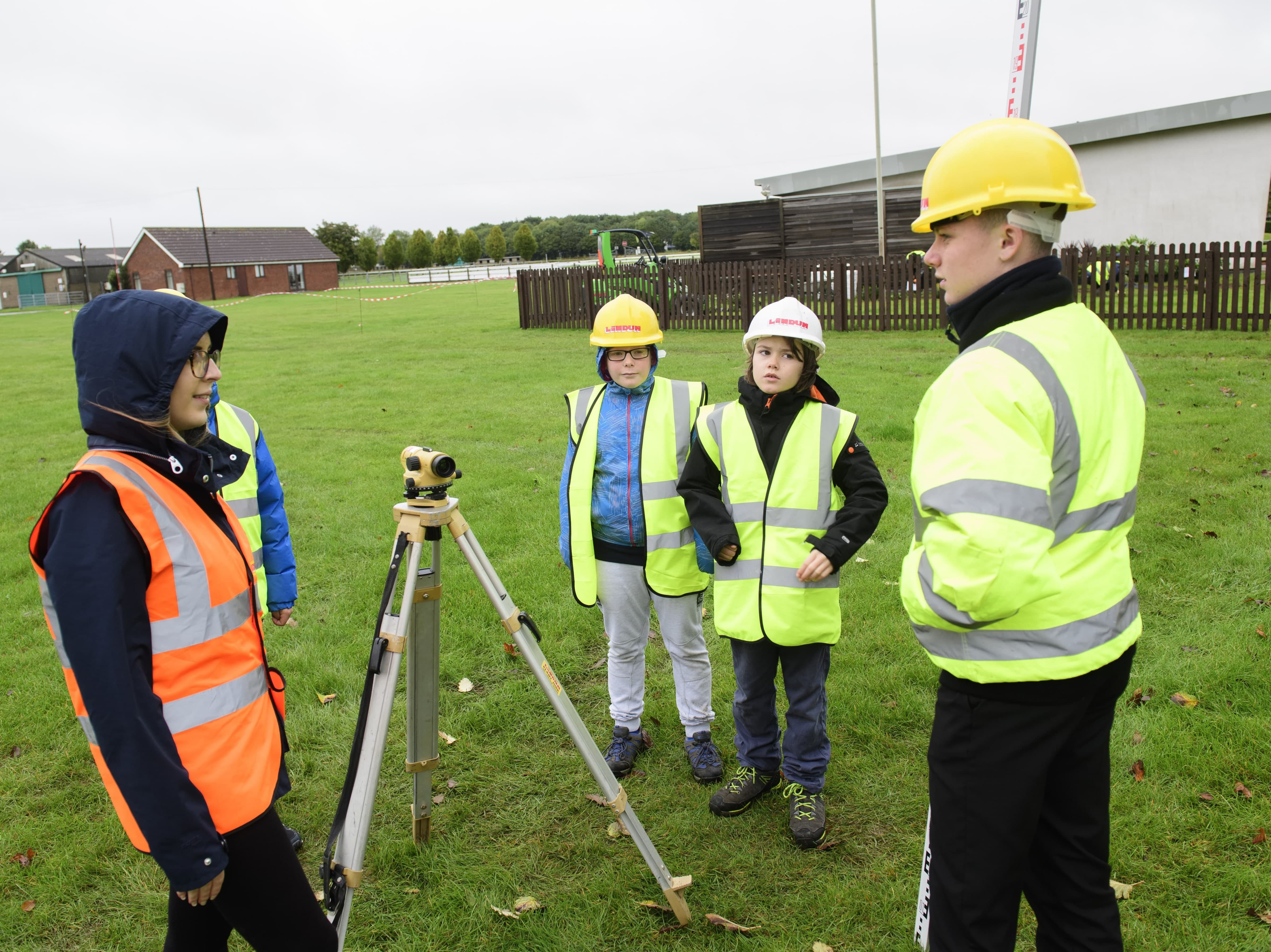 Young girl operating equipment with other children watching on, all wearing yellow high vis jackets