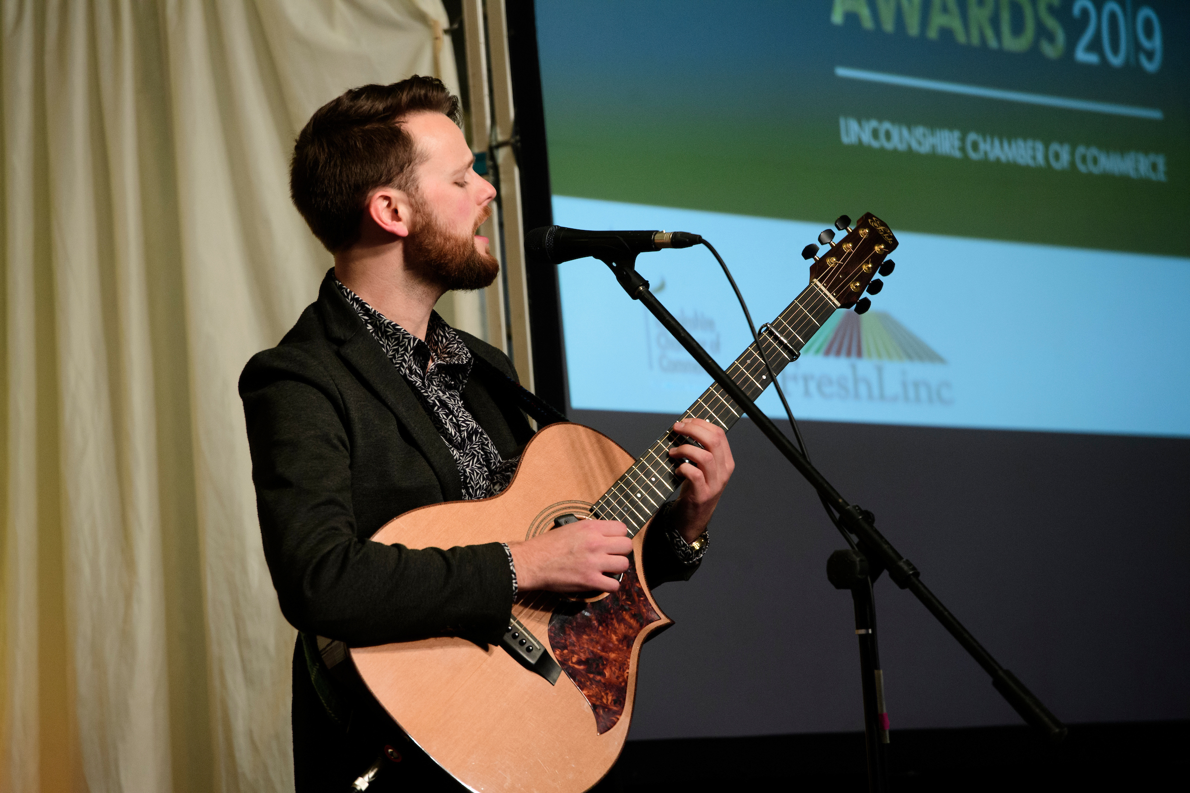 A young man with acoustic guitar, Elliott Morris, playing onstage at the South Holland Business Awards 2019