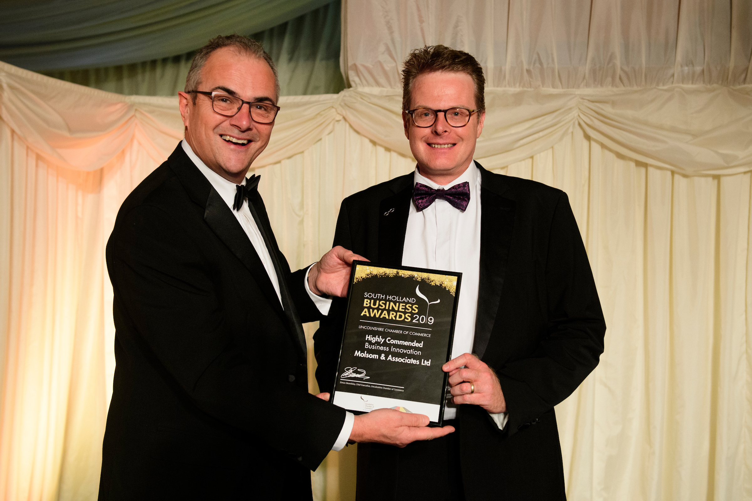 Two men in formal evening wear holding trophies and certificates and smiling at the South Holland Business Awards 2019
