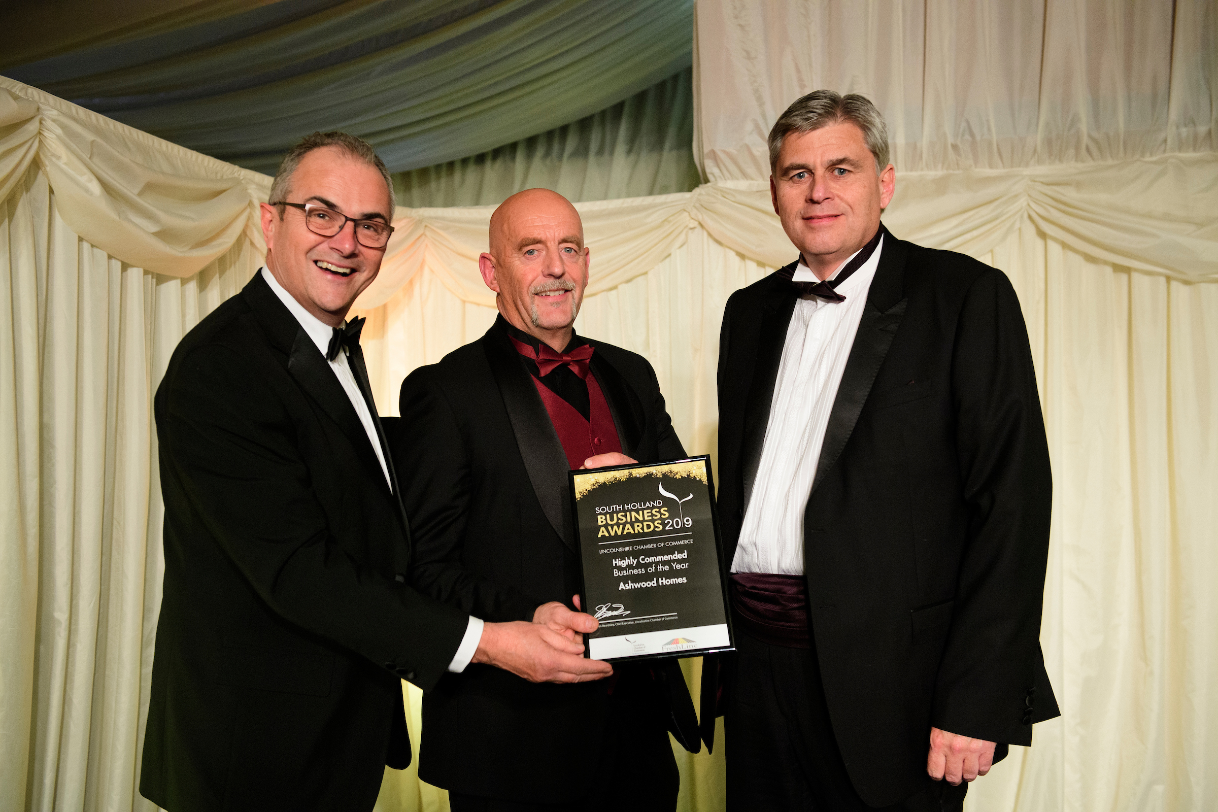 Three men in formal evening wear holding trophies and certificates and smiling at the South Holland Business Awards 2019