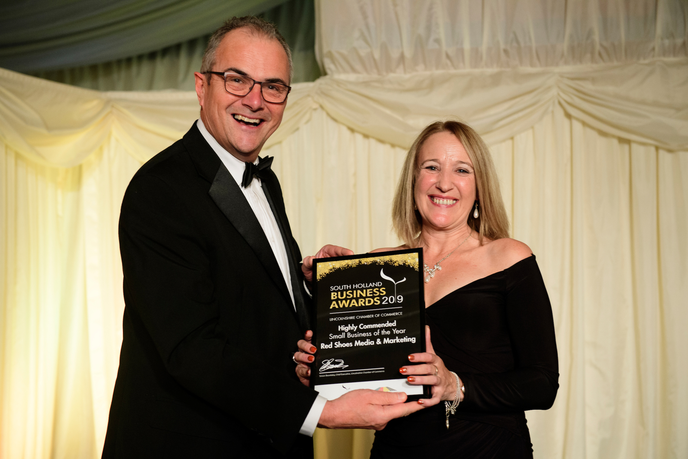 A man and a woman in formal eveningwear at the South Holland Business Awards 2019, holding a framed certificate