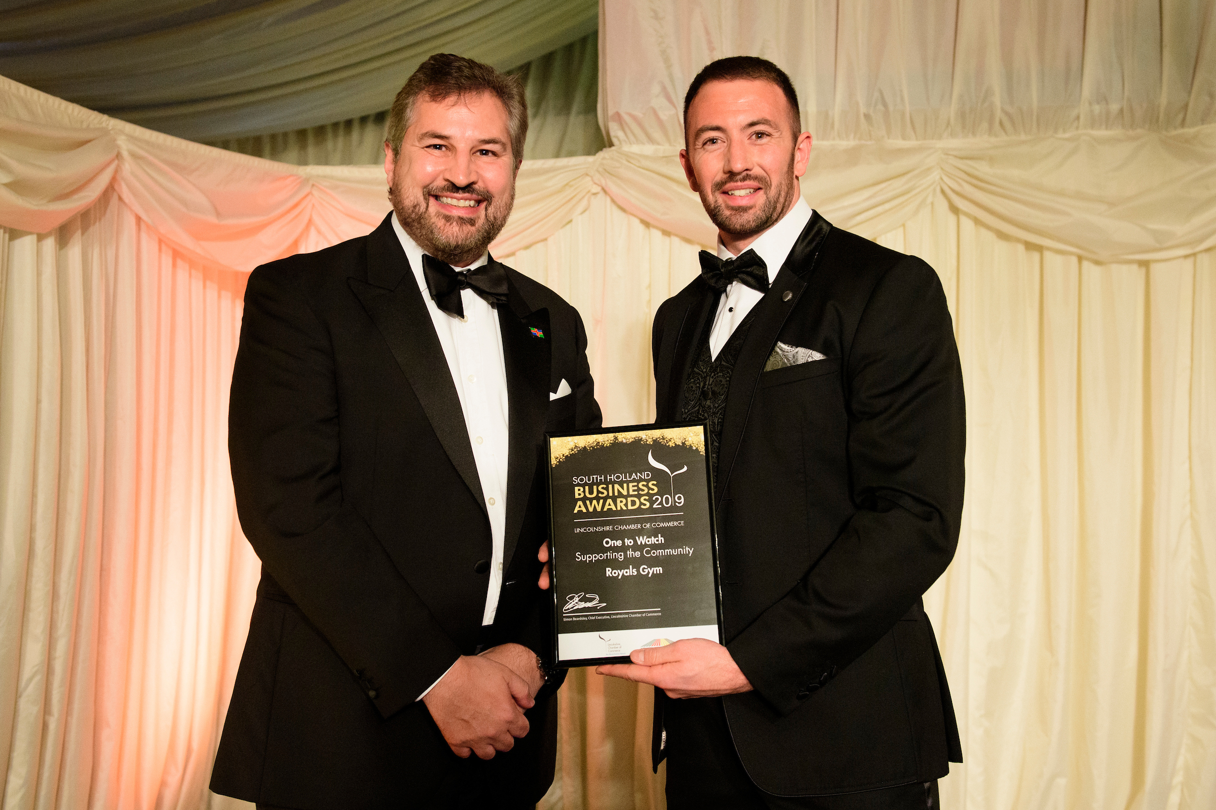 Two men, Gary Headland is the Chairman of Lincolnshire Chamber of Commerce, and a man representing a winning company, at the South Holland Business Awards 2019