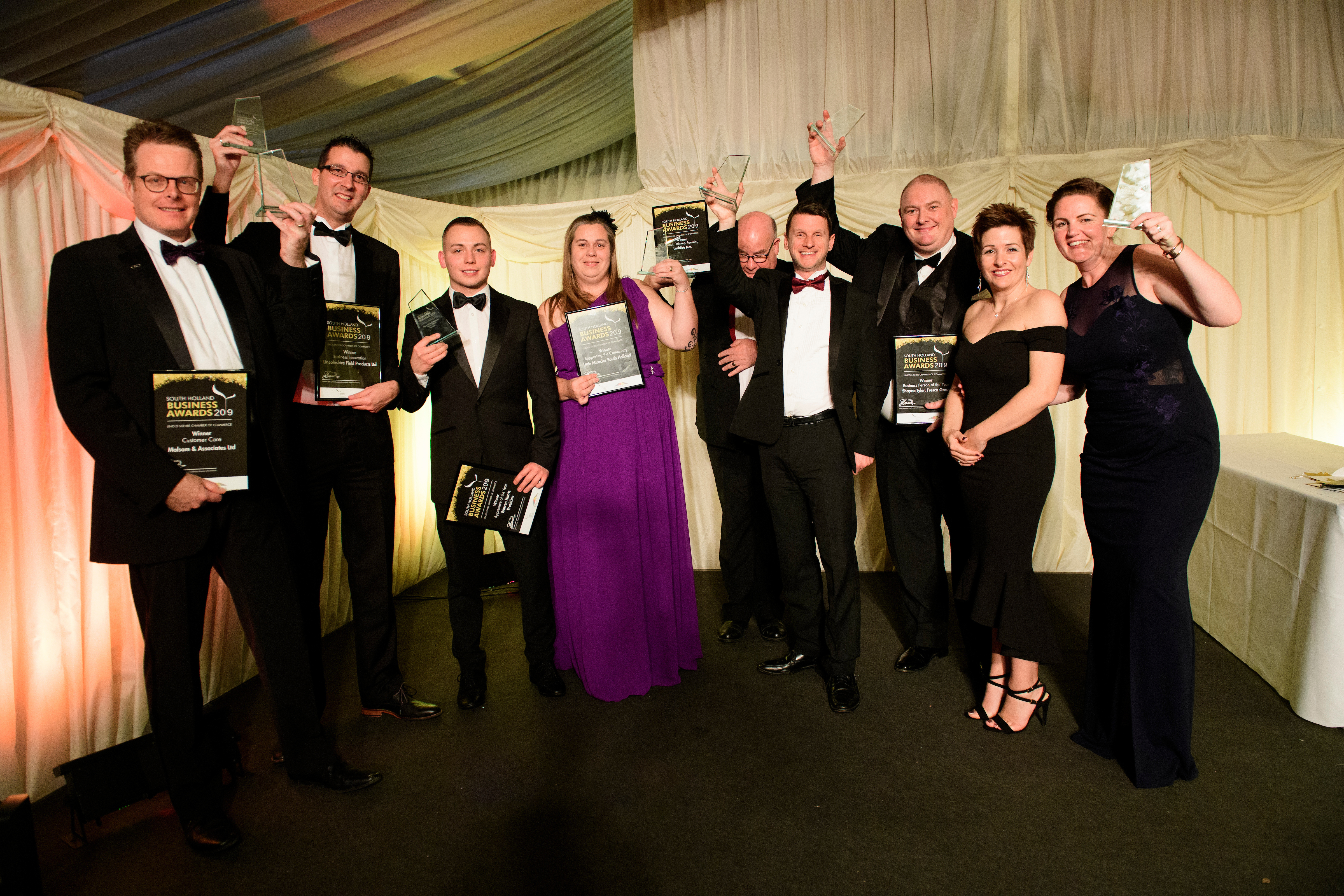 Group of people in eveningwear holding framed certificates, trophies, posing and smiling at the South Holland Business Awards 2019