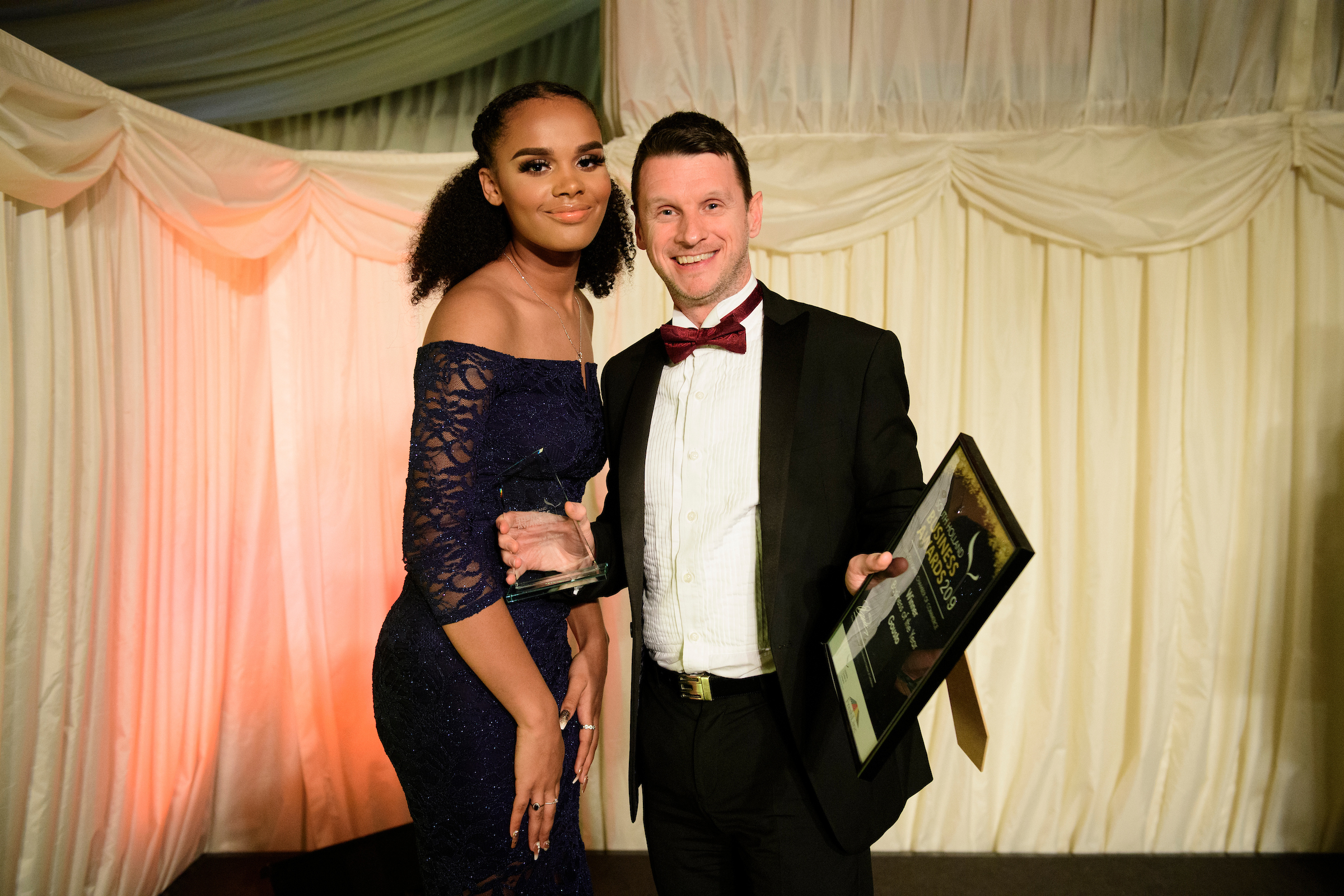 Young woman in off shoulder dress next to man in suit and bowtie, holding trophy and certificate at the South Holland Business Awards 2019