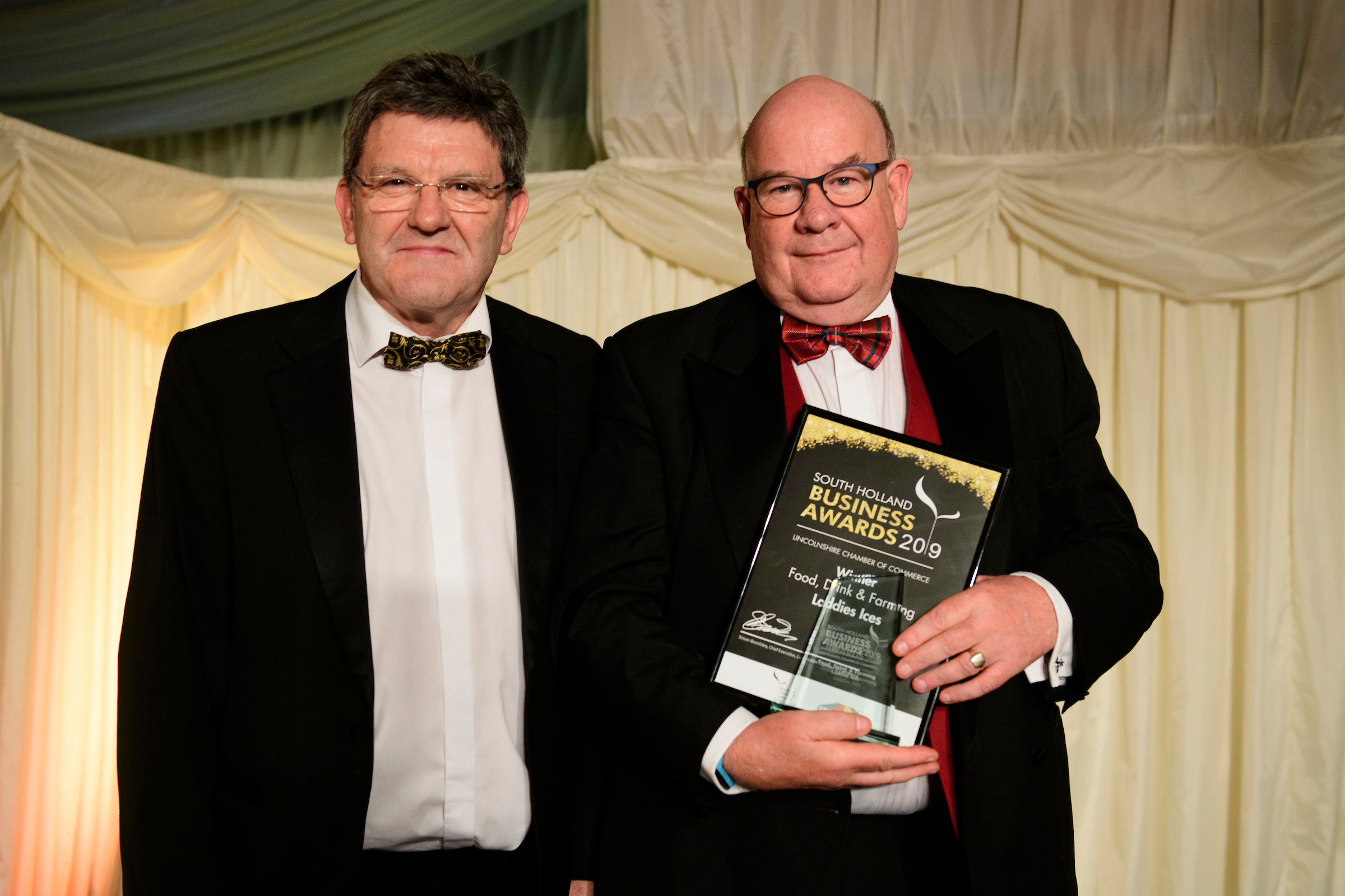 Two men in suits and bowties, one is holding a framed certificate and trophy, at the South Holland Business Awards 2019