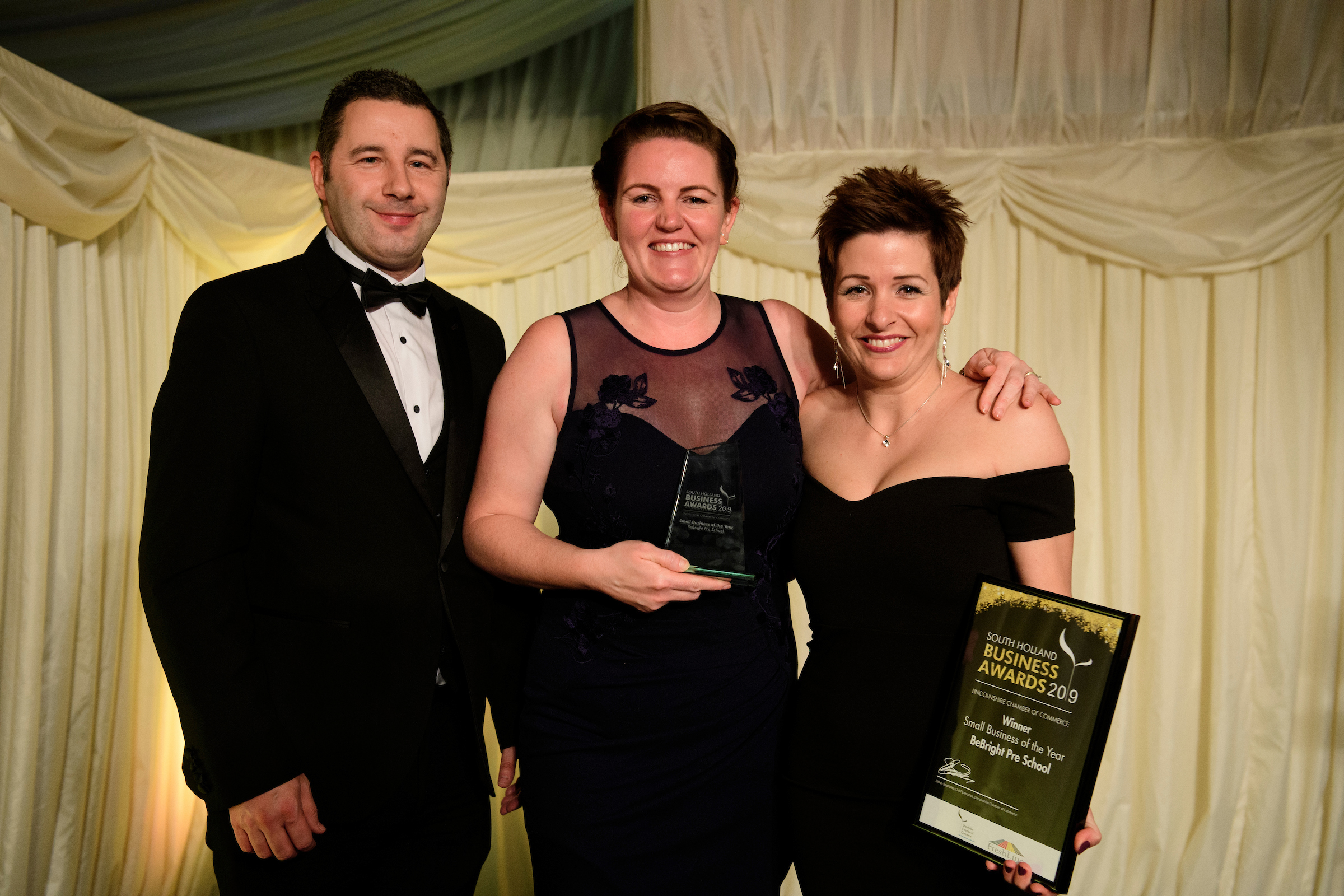 Two women in black dresses next to a man in suit and bowtie with a trophy and certificate at the South Holland Business Awards 2019