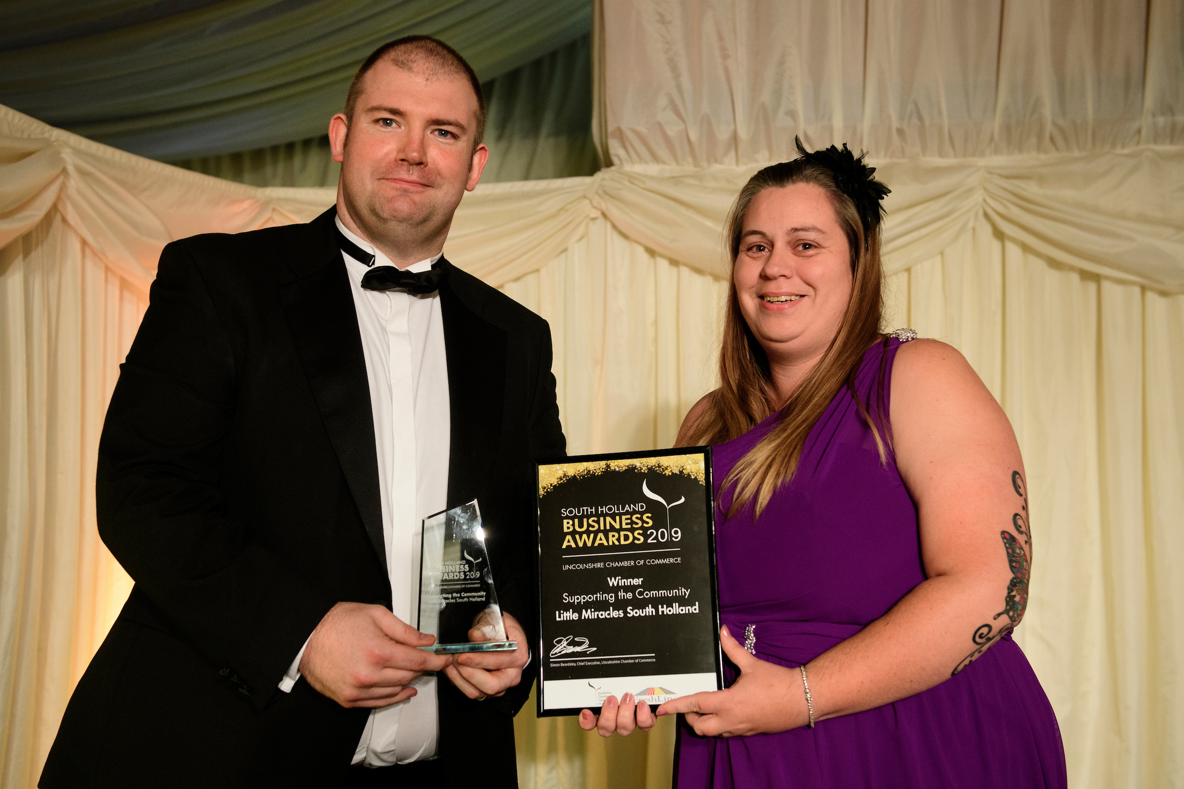 A man and woman in eveningwear holding certificate and trophy at the South Holland Business Awards 2019