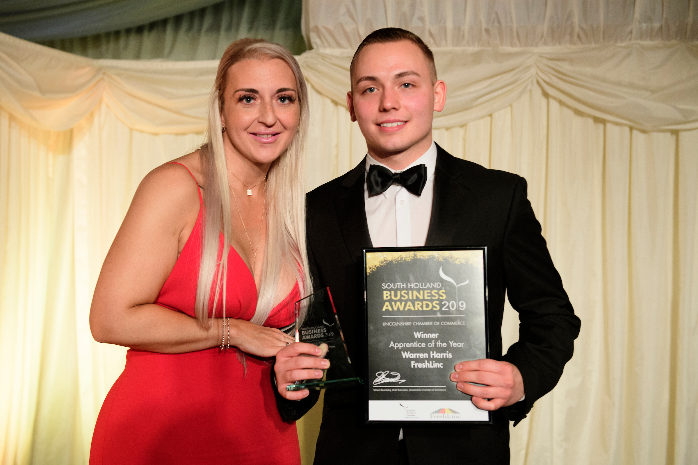 A young man holding a trophy and framed certificate next a blonde woman in red dress at the South Holland Business Awards 2019