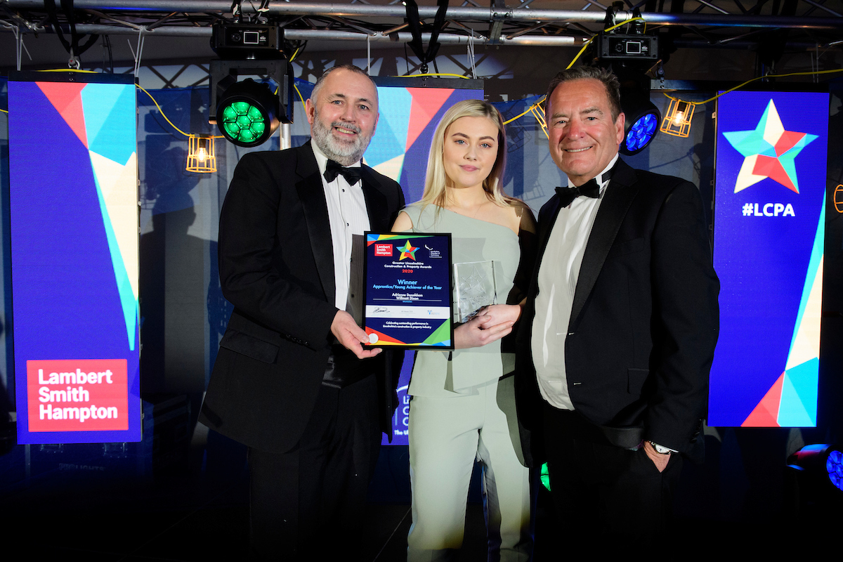 Two men and a young woman at an awards show, holding a certificate