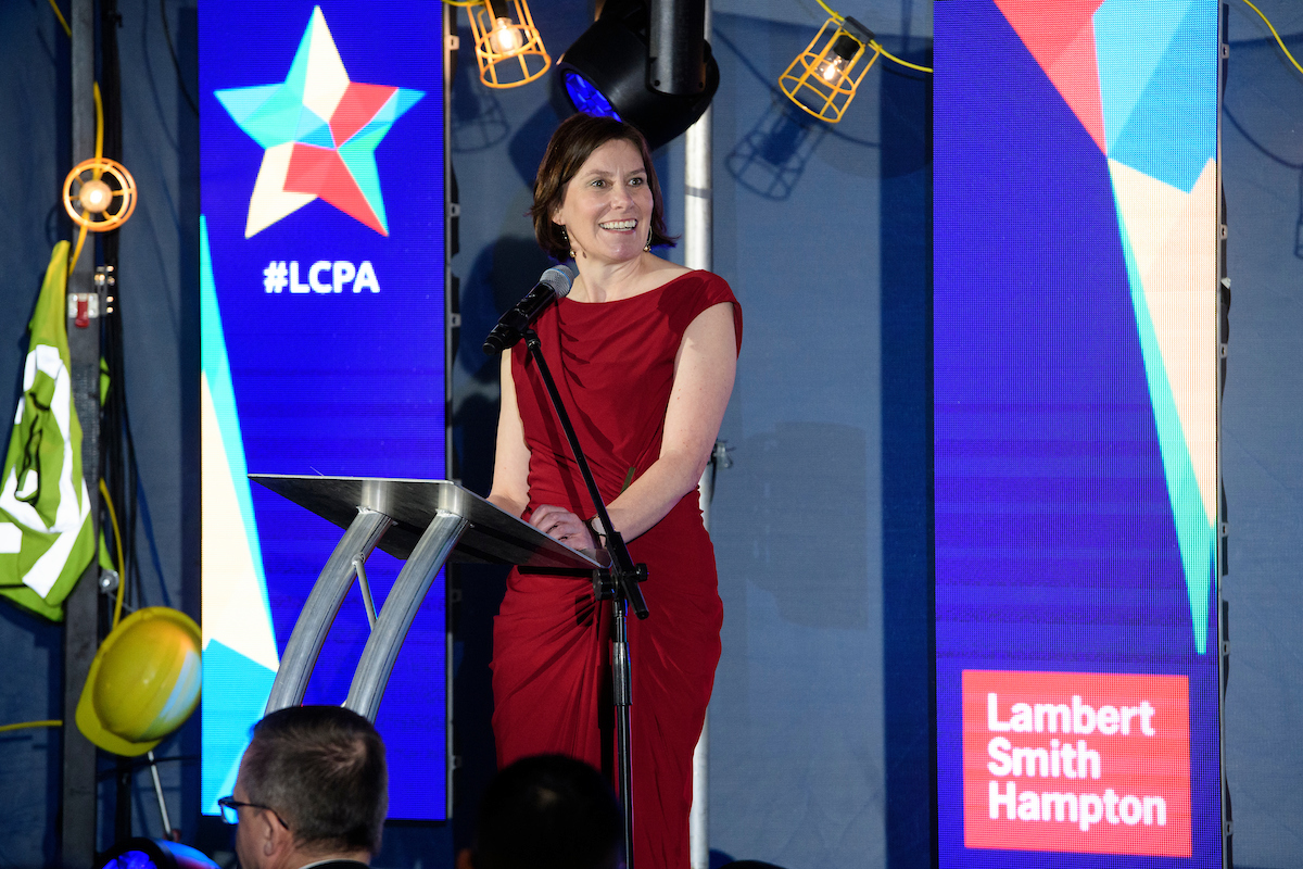 Caroline Killeavy, Chief Executive, YMCA Lincolnshire at The Greater Lincolnshire Construction and Property Awards 2020 wearing a red dress on stage