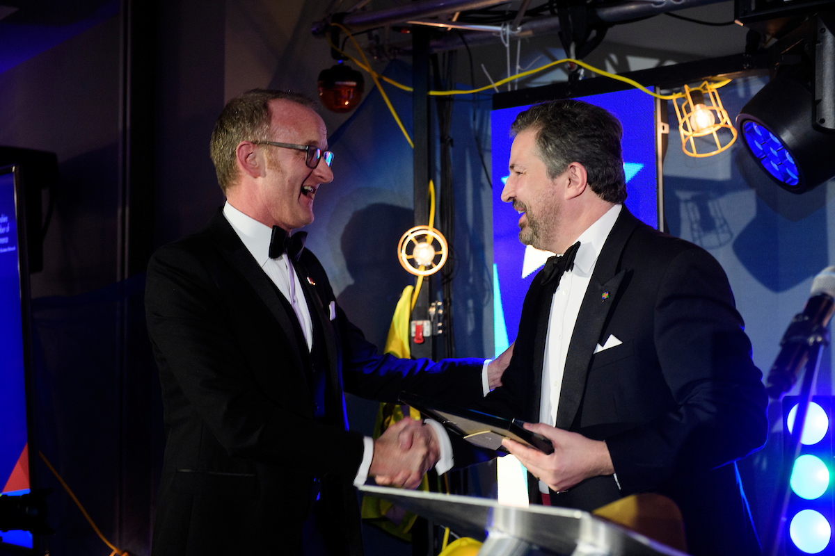 Two men in eveningwear, Tim Downing and Gary Headland, shaking hands at The Greater Lincolnshire Construction and Property Awards 2020