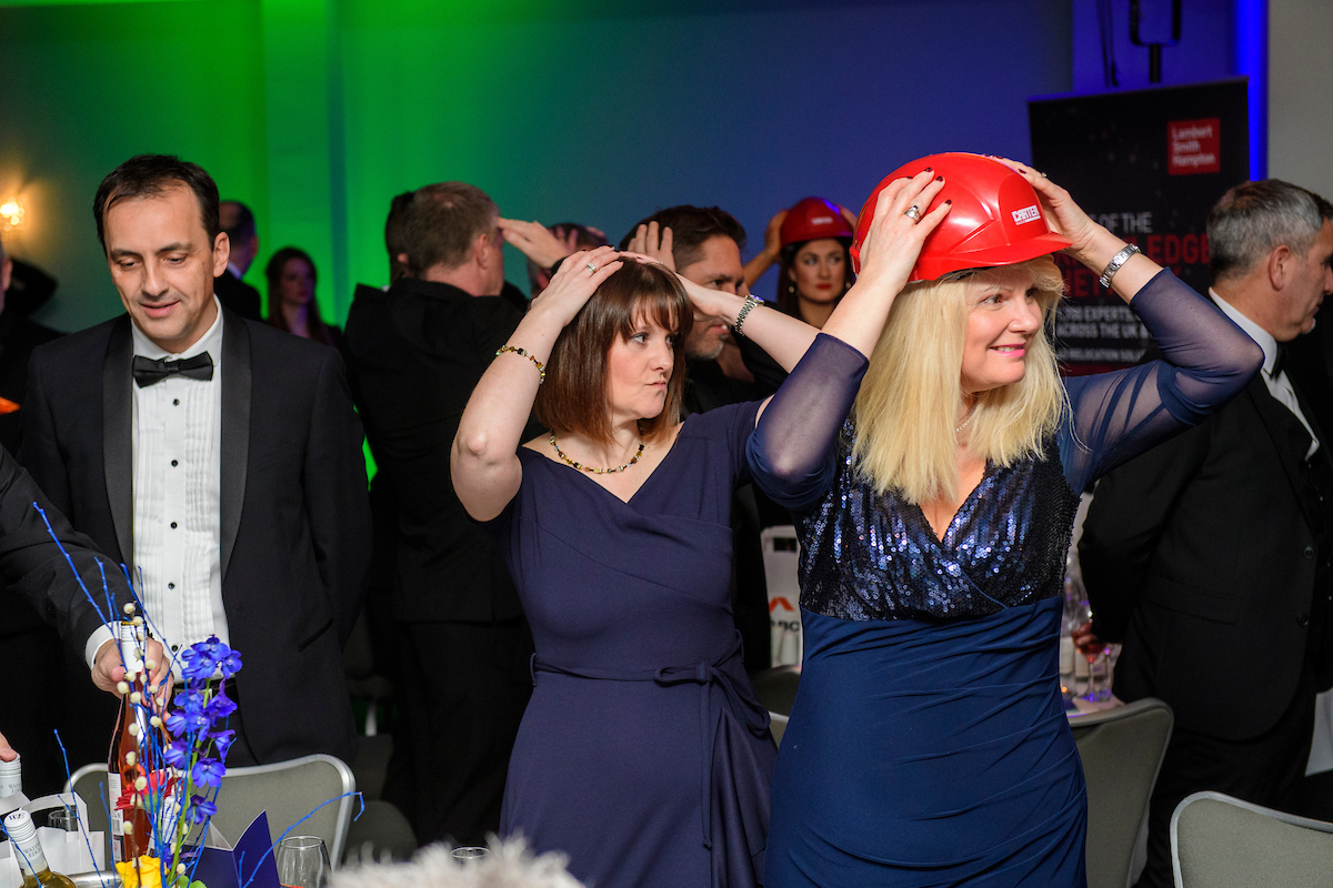 Several people wearing eveningwear and red hard hat standing up at an awards show with their hands on head