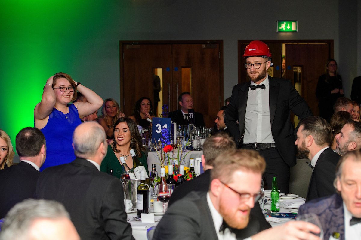 Young woman in blue dress and man wearing eveningwear and red hard hat standing up at an awards show
