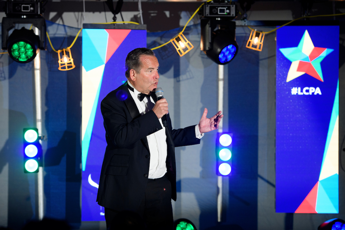 Picture of a man wearing a black suit and bowtie holding a microphone with digital screens showing blue background and #LCPA text