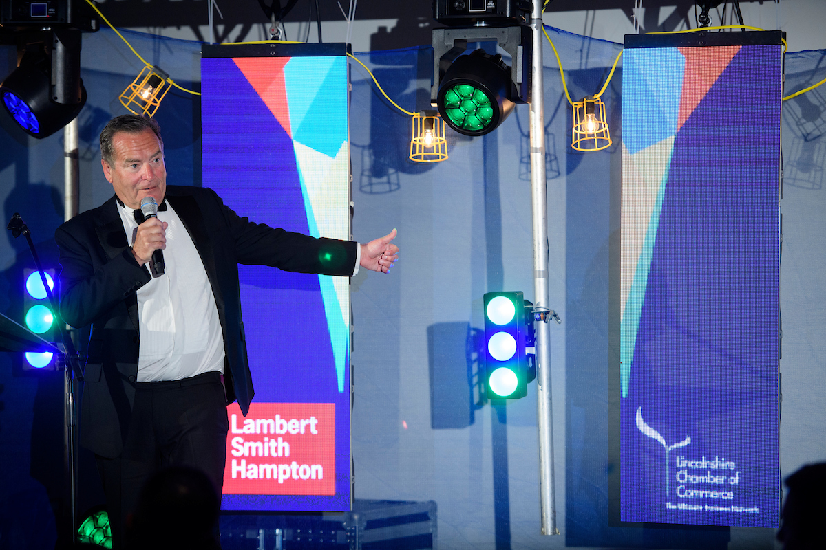 Greater Lincolnshire Construction & Property Awards 2020 host Jeff Stelling on stage with microphone and Lincolnshire Chamber of Commerce logo