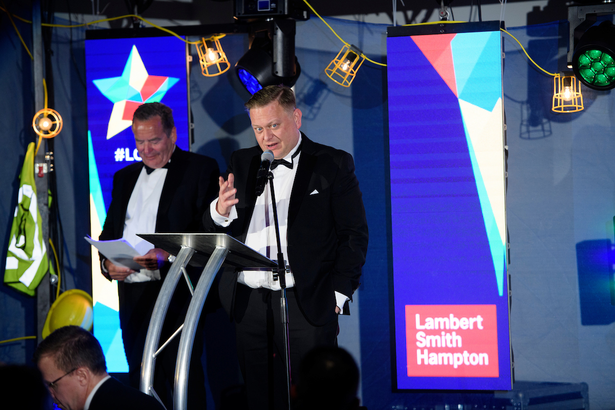 Two men on stage at an awards show with tv screen in the background