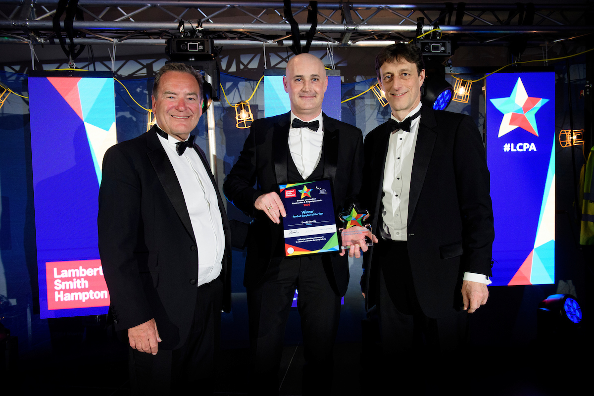 Three men in formal evening wear holding trophies and certificates and smiling