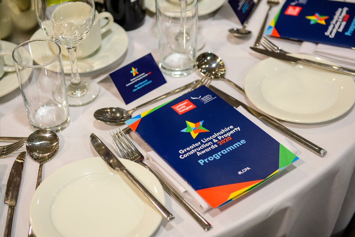 Picture of a set table with white table cloth, cutlery and plates, a blue booklet lies on top of one plate with text The Greater Lincolnshire Construction and Property Awards 2020