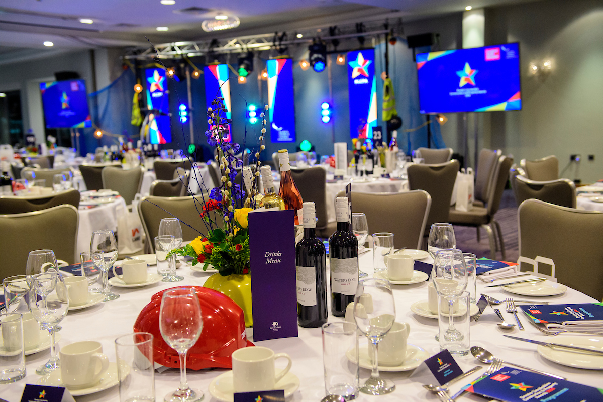Set up of an awards dinner, picture of a table with glasses, plates, cutlery, a red hard hat and flower arrangement at The Greater Lincolnshire Construction and Property Awards 2020