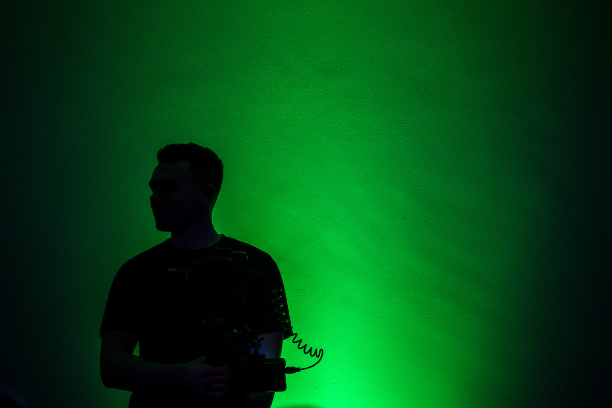 Person with video camera backlit in green light