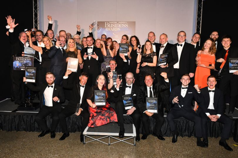 Picture of a group of people in formal evening wear sitting and standing at the Business Awards 2019