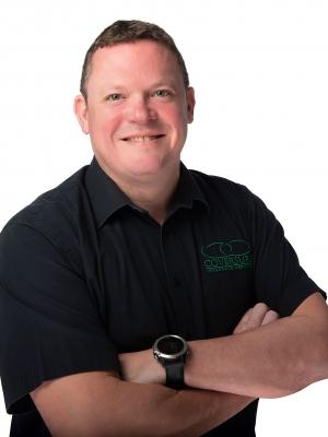 Man with folded arms and dark shirt smiling at camera
