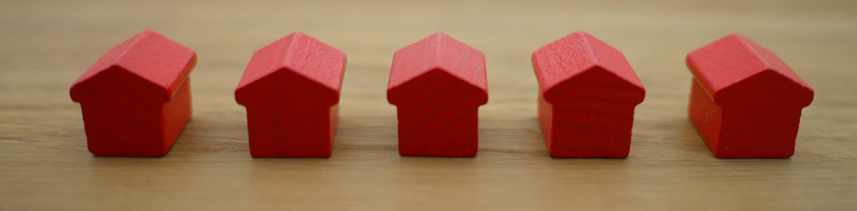 Five miniature red houses from a Monopoly game in a row on wooden table