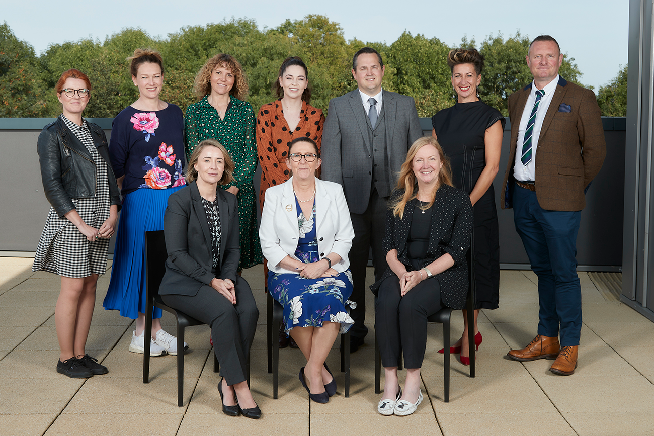 Group of men and women sitting and standing posing, they are the new Greater Lincolnshire LEP Visitor Economy Board